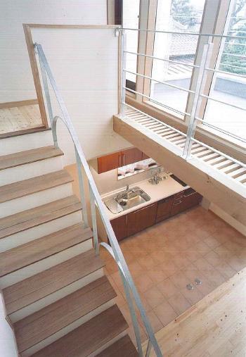 2階から見下ろしたダイニングキッチン。吹き抜け大きな窓から下へ自然光がたっぷり降りそそぎます。テラコッタタイルの床は奥様のお気に入り。