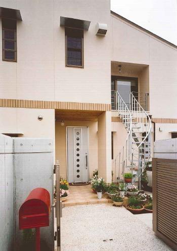 素焼きのタイルに床に円弧を描く鋼製外階段、2世帯住宅では 子世帯が直接2階へ帰宅できるようにこんな工夫も